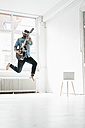 Man with guitar wearing Virtual Reality Glasses jumping in the air in a loft - JOSF01534