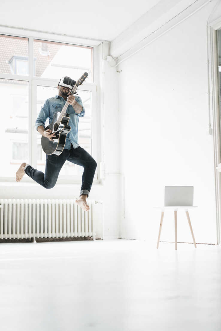 Man with guitar wearing Virtual Reality Glasses jumping in the air in a loft - JOSF01534 - Joseffson/Westend61