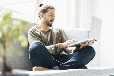 Portrait of man sitting on the couch using laptop - JOSF01543