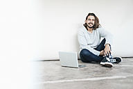 Portrait of smiling man with laptop sitting on the floor - JOSF01546