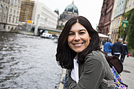 Germany, Berlin, portrait of smiling young woman in the city - ABZF02173