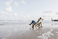 Woman sitting on deckchair on the beach - KNSF02540
