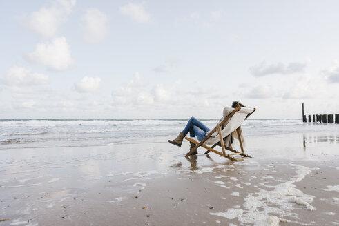 Woman sitting on deckchair on the beach - KNSF02540