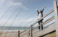 Happy woman standing on boardwalk at the beach with raised arms - KNSF02543