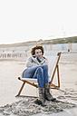 Woman sitting on deckchair on the beach - KNSF02546