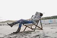 Happy woman sitting on deckchair on the beach - KNSF02549
