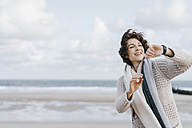Woman on the beach looking at her smartwatch - KNSF02552