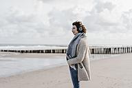 Woman standing on the beach with headphones - KNSF02558