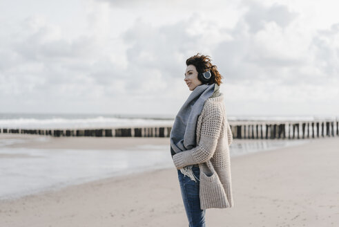 Woman standing on the beach with headphones - KNSF02558