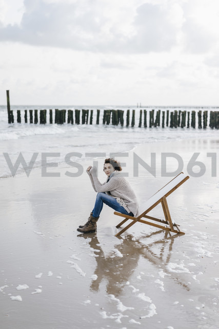 Woman sitting on deckchair on the beach - KNSF02573
