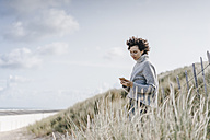 Woman standing in beach dune using cell phone - KNSF02576