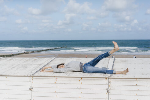 Woman lying on wooden box on the beach - KNSF02585