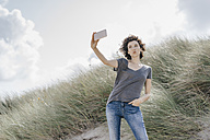 Woman standing in beach dune taking a selfie - KNSF02588