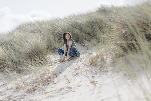 Woman sitting in beach dune - KNSF02591