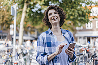 Happy woman with cell phone in the city - KNSF02594