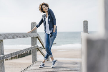 Portrait of smiling woman standing on boardwalk at the beach - KNSF02600