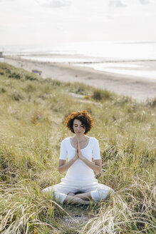 Woman practicing yoga in beach dune - KNSF02615