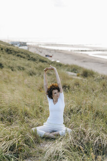 Woman stretching in beach dune - KNSF02618