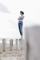 Woman standing on wooden stake on the beach - KNSF02621