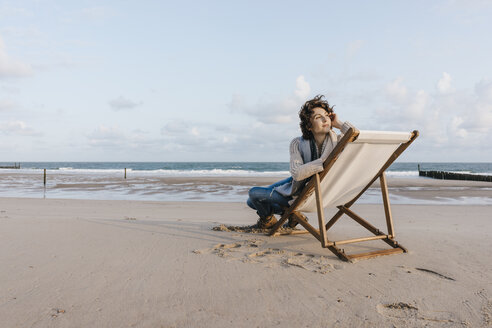 Woman sitting on deckchair on the beach - KNSF02633