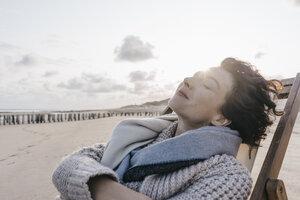 Woman relaxing in deckchair on the beach - KNSF02636