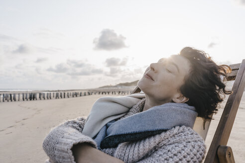 Woman relaxing in deckchair on the beach - KNSF02636