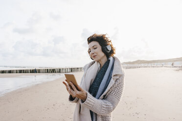 Woman on the beach with cell phone and headphones - KNSF02639