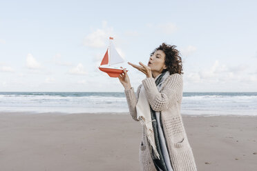 Woman blowing at toy boat on the beach - KNSF02651