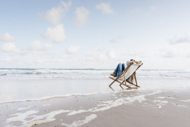 Woman sitting on deckchair on the beach - KNSF02654