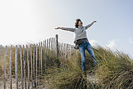 Happy woman standing in beach dune - KNSF02660