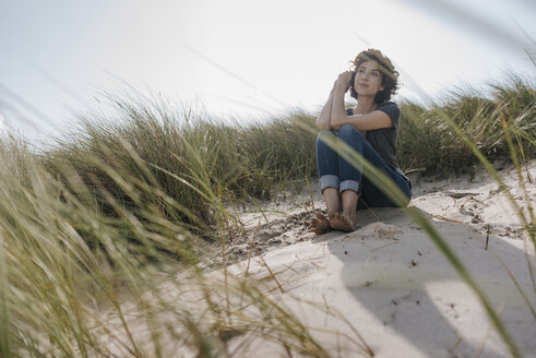 Woman sitting in beach dune - KNSF02672