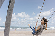 Happy woman on a swing on the beach - KNSF02678
