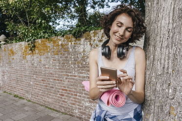 Smiling woman with mat, headphones and cell phone on pavement - KNSF02681
