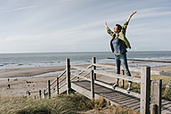 Woman standing on boardwalk at the beach with raised arms - KNSF02687