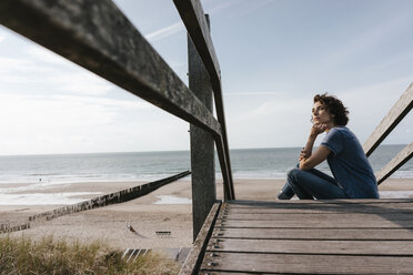 Woman sitting on boardwalk at the beach - KNSF02690