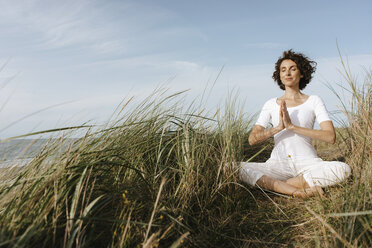 Woman practicing yoga in beach dune - KNSF02696