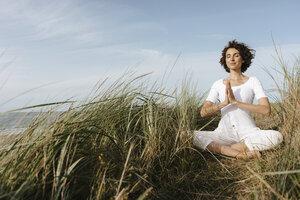 Woman practicing yoga in beach dune - KNSF02696
