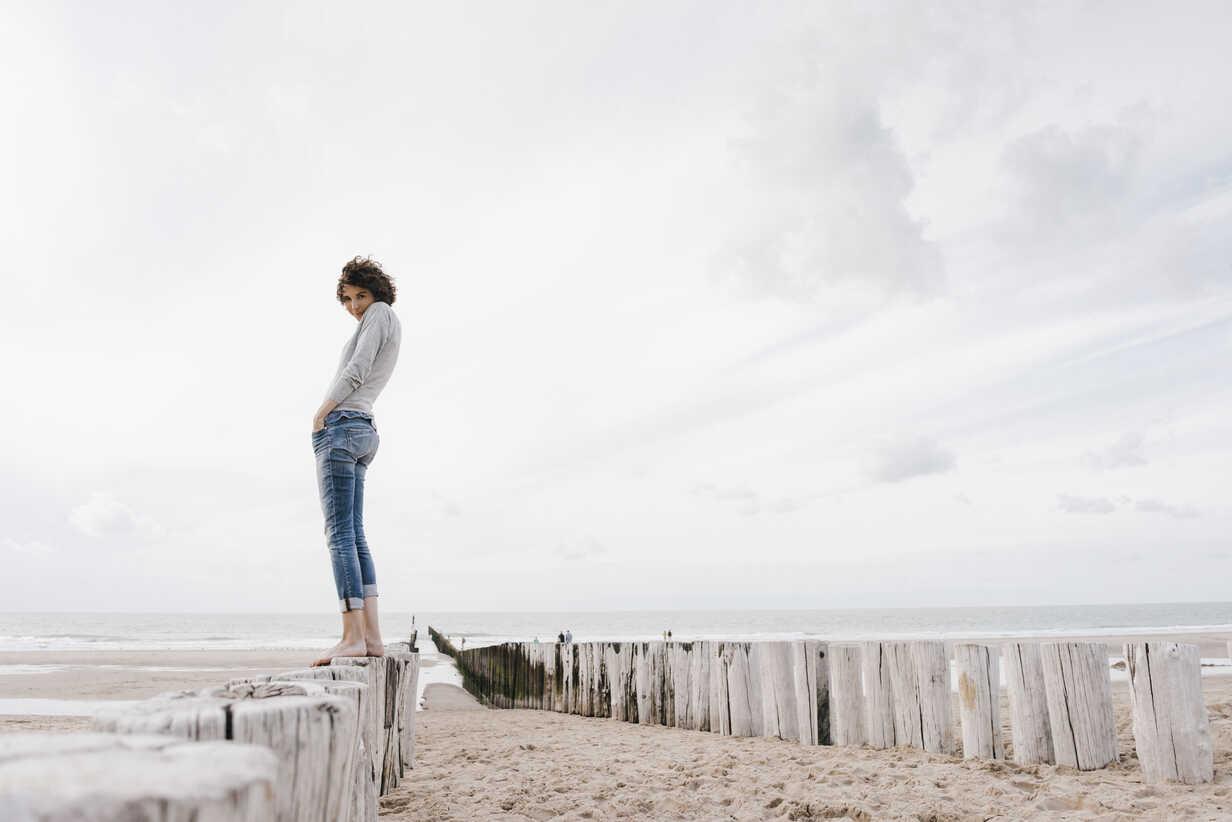 Woman standing on wooden stake on the beach - KNSF02699 - Kniel Synnatzschke/Westend61