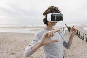 Woman on the beach wearing VR glasses - KNSF02702