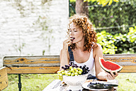 Redheaded young woman eating grapes in summer - FMKF04424