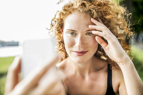 Portrait of freckled young woman taking selfie with cell phone - FMKF04433