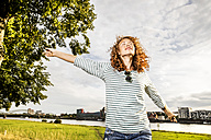 Germany, Cologne, young woman enjoying sunlight - FMKF04439