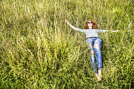 Young woman relaxing on a meadow - FMKF04442