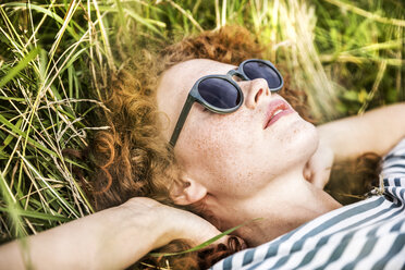 Young woman wearing sunglasses relaxing on a meadow - FMKF04445