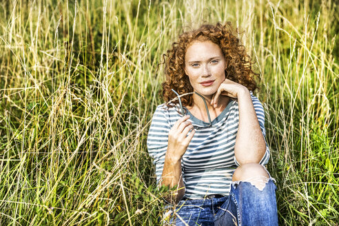 Young of woman sitting on a meadow - FMKF04448