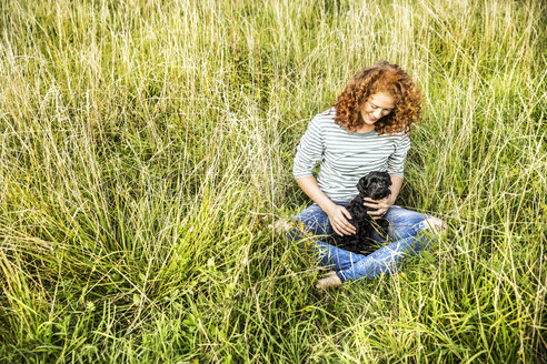 Young woman relaxing on a meadow with her dog - FMKF04451