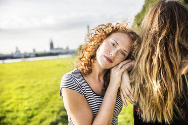 Germany, Cologne, portrait of redheaded young woman with friend - FMKF04454
