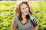 Portrait of redheaded young woman enjoying beverage - FMKF04457