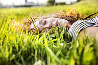 Portrait of redheaded young woman with eyes closed lying on meadow - FMKF04460