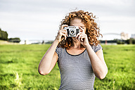 Young woman on a meadow taking picture of viewer with camera - FMKF04466